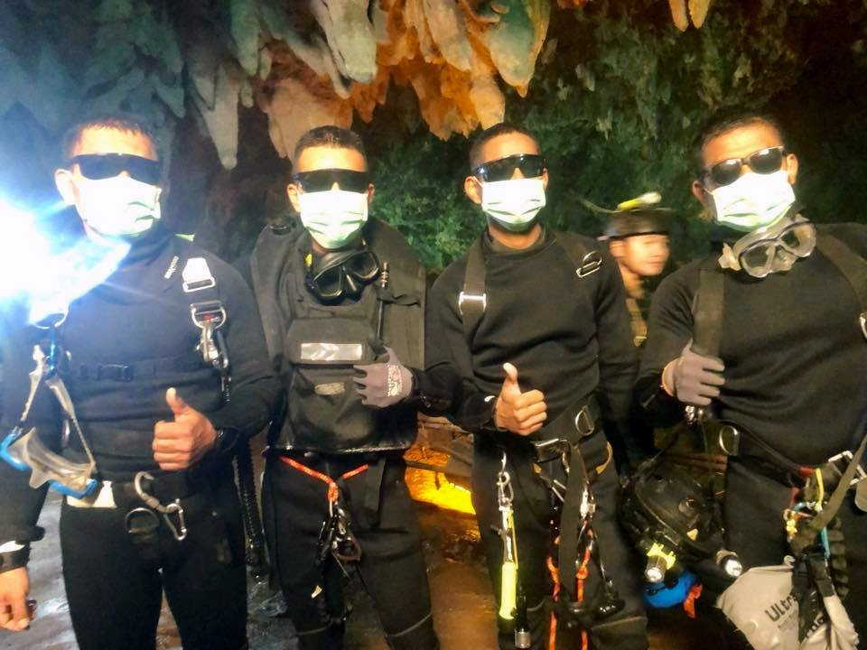 File: The last four Thai Navy SEALs giving a thumbs up after exiting safely from the Tham Luang cave following the rescue of the remaining four boys and their coach.