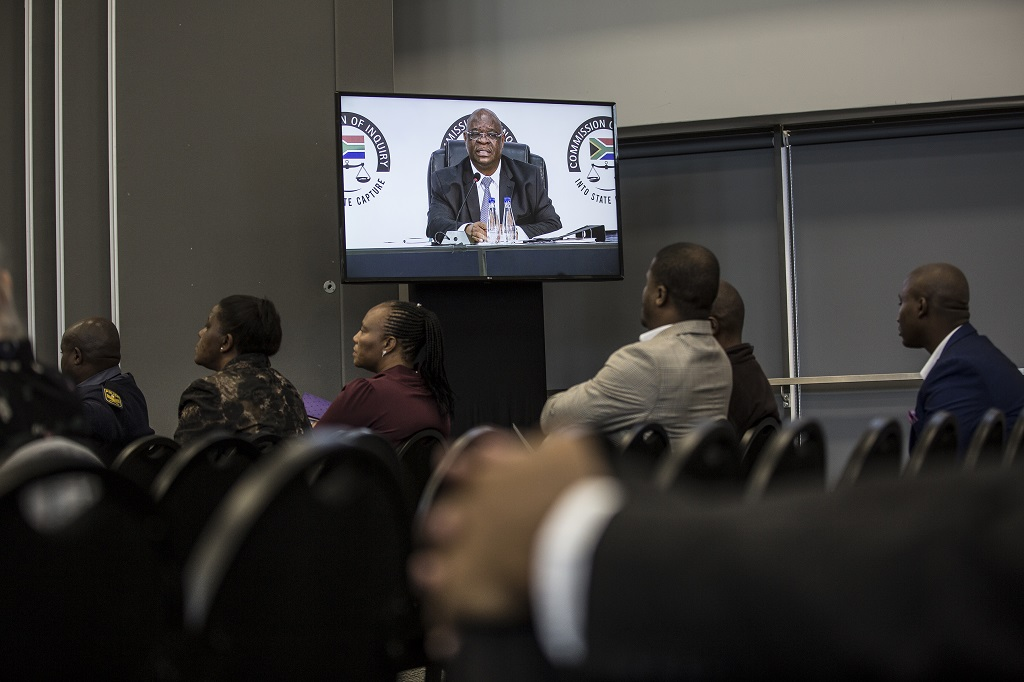 People listen to Chairperson Advocate Deputy Chief Justice Raymond Zondo who opens proceedings during the first public hearing on alleged corruption under scandal-tainted former South African president, who was ousted earlier this year, at the Commission of Inquiry, in Johannesburg, on August 20, 2018.