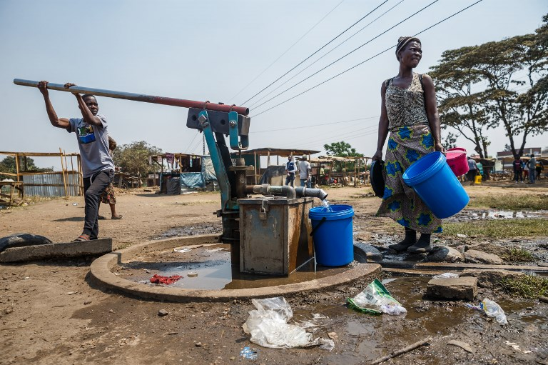 A young boy pumps water from a borehole as a woman collects water into buckets in Glen View, a suburb of Zimbabwe's capital Harare where the cholera outbreak was first detected, on September 19, 2018.