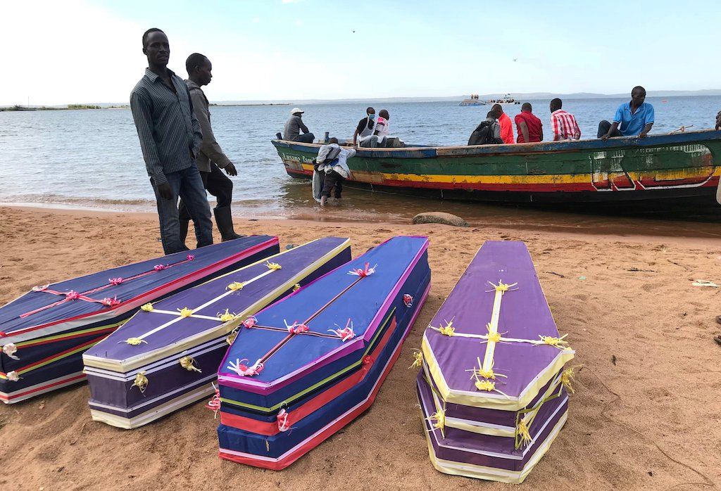 Dozens of wooden coffins lined the shore on Saturday, waiting to be seen by families as police and volunteers sought to keep hundreds of curious locals at bay.