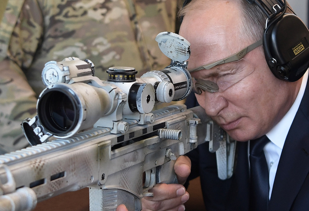Russian President Vladimir Putin looks through the scope as he shoots a Chukavin sniper rifle (SVC-380) during a visit to the military Patriot Park in Kubinka, outside Moscow.