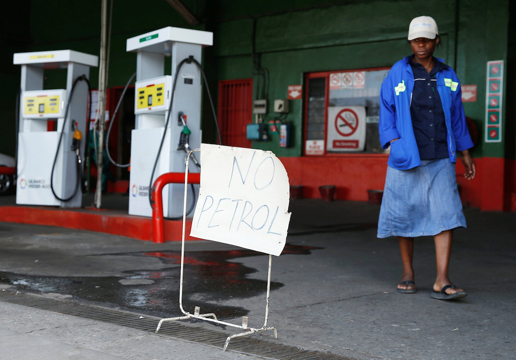 "A woman walks past a ""No Petrol"" sign at a fuel station in Harare, Zimbabwe."