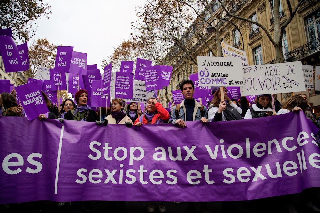 Participants walk with a banner reading 'Stop sexist and sexual violence' as they take part in a rally in Paris.