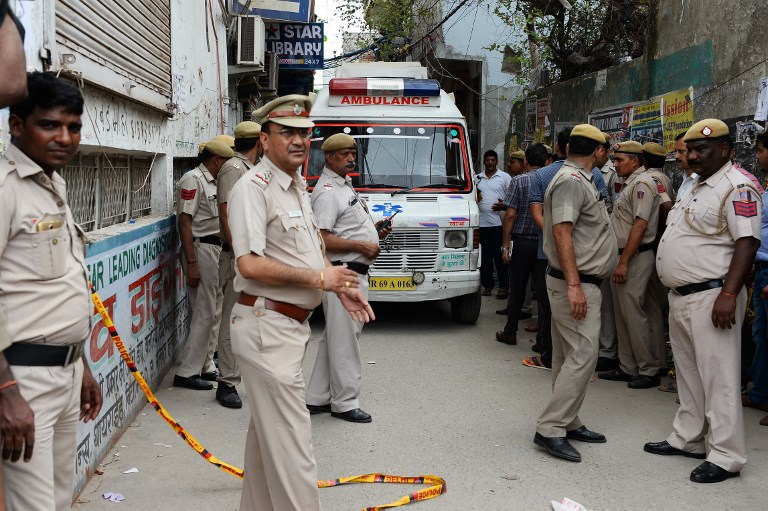 An ambulance enters the street where 11 family members were found dead inside their home in the neighbourhood of Burari in New Delhi on July 1, 2018.