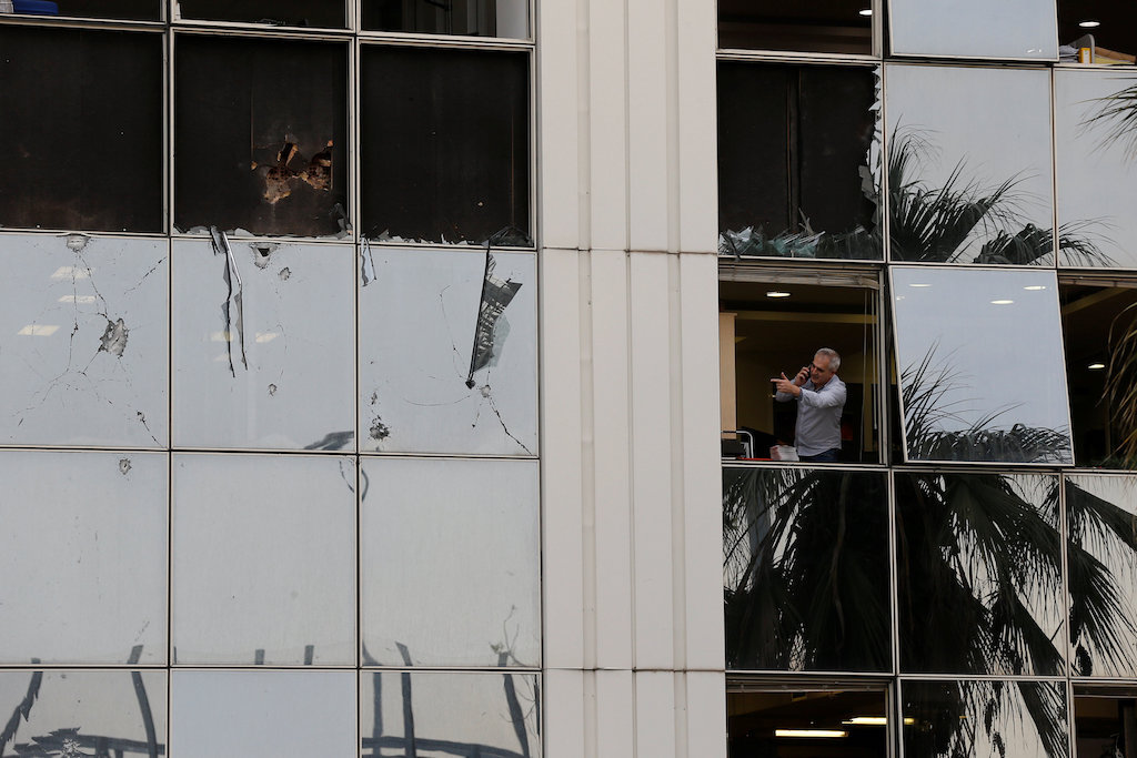 A man looks out from a broken window after a bomb blast outside the Greek SKAI TV building in Athens.