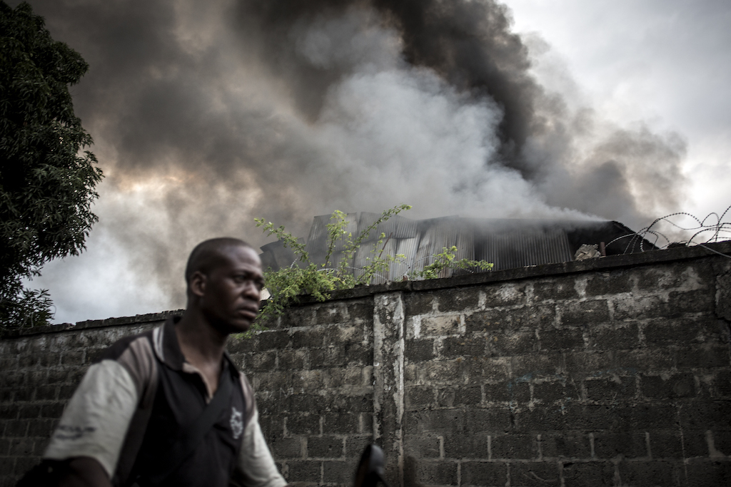 A man walks past smoke rising from a fire at the independent national electoral commission's (CENI) warehouse in Kinshasa, ten days ahead of presidential elections.