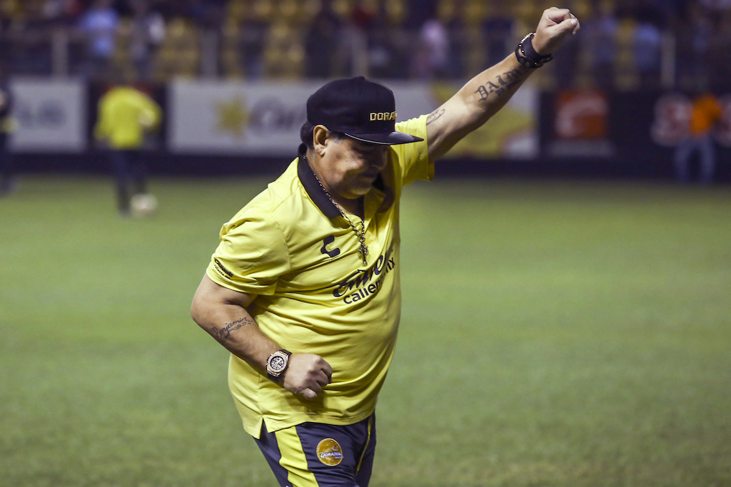 In videos posted online, Diego Maradona can be seen trying to lunge at the fans as security guards hold him back.