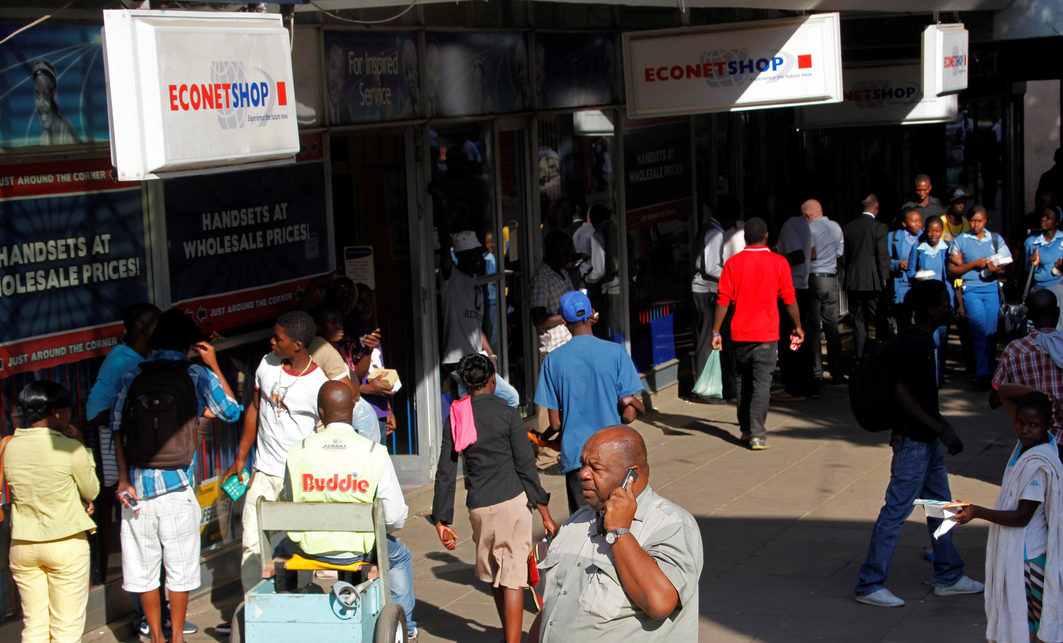 File: A Zimbabwean man speaks on his phone outside a branch of mobile service provider Econet Wireless in central Harare, June 6, 2014.