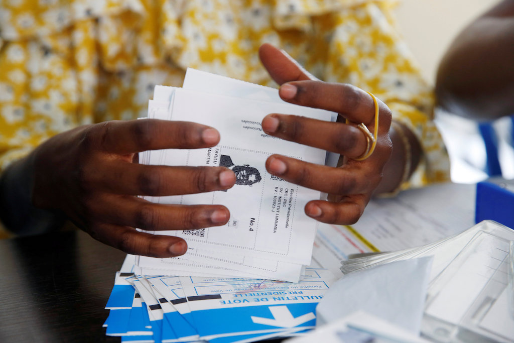 A Congo's Independent National Electoral Commission (CENI) official holds a ballot of Martin Fayulu during the counting of presidential elections ballots.