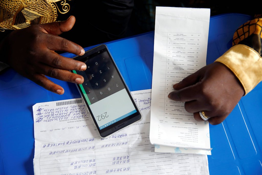 An official from Congo's Independent National Electoral Commission (CENI) uses his phone to calculate the numbers of presidential election votes.