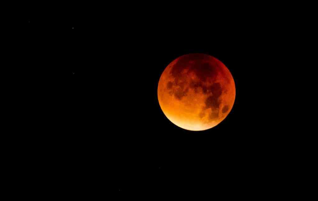 "File: In a total lunar eclipse, the moon never goes completely dark. Rather, it takes on a reddish glow from refracted light, hence the ""blood moon"" moniker."