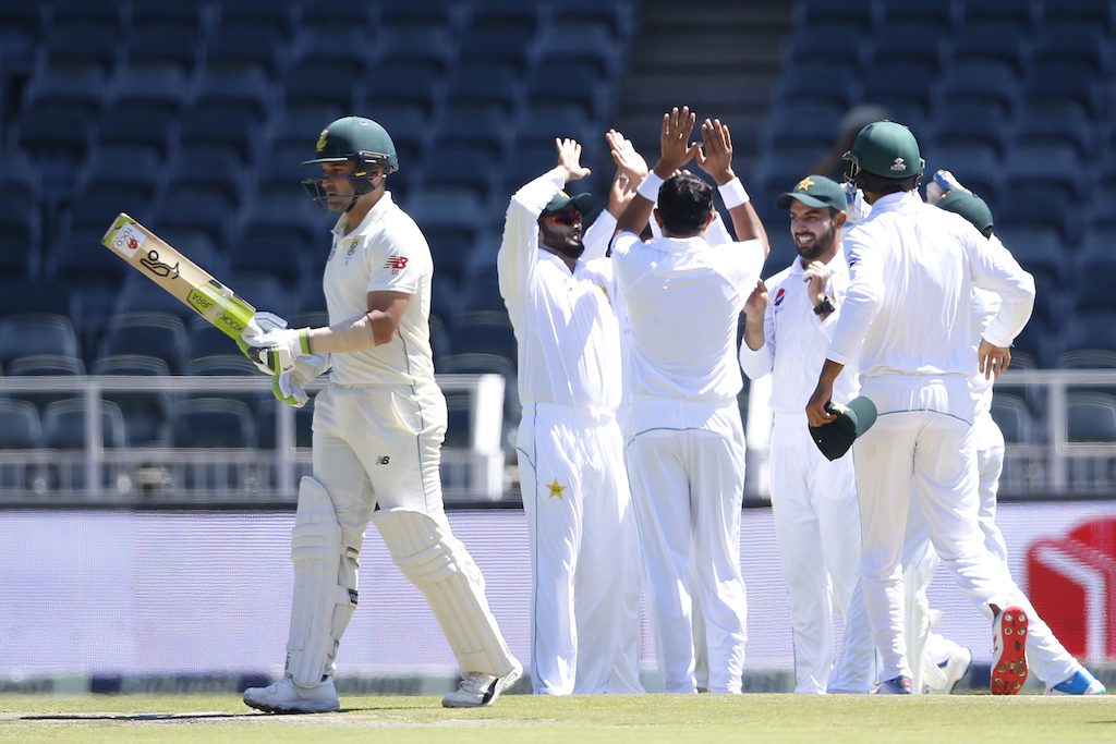 The Pakistan team celebrates the dismissal of South African batsman Dean Elgar (L) during the first day of the third Cricket Test match.