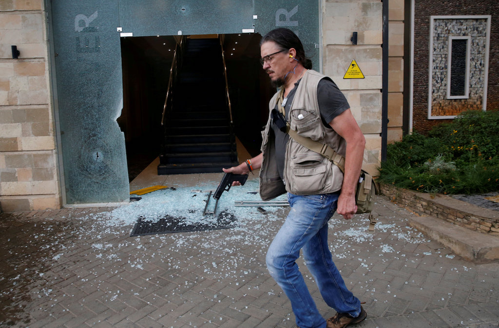 Serge Medic, the Swiss owner of a security company carries his firearm as he walks at the scene where explosions and gunshots were heard at the Dusit hotel complex in Nairobi, Kenya on 15 January 2019.