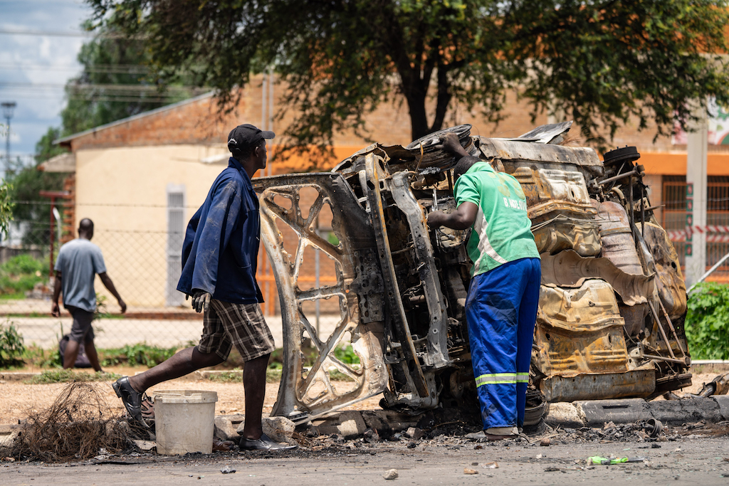Scrap metal collectors salvages sellable parts from a car shell burnt during the protests in Emakhandeni township, Bulawayo.