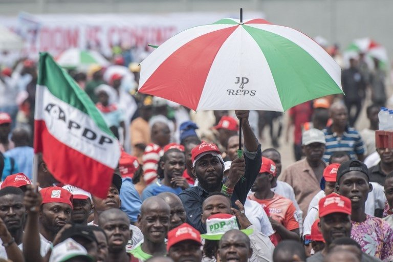 People's Democratic Party (PDP) supporters wave party flags during a campaign rally at Tafawa Balewa square in Lagos on February 12, 2019.