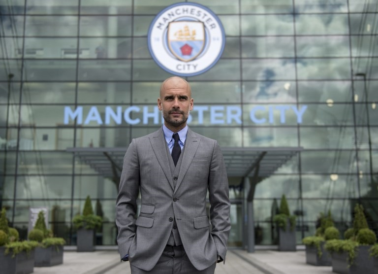 Manchester City's Spanish football coach Pep Guardiola poses for pictures outside the Etihad Stadium in Manchester, northern England.