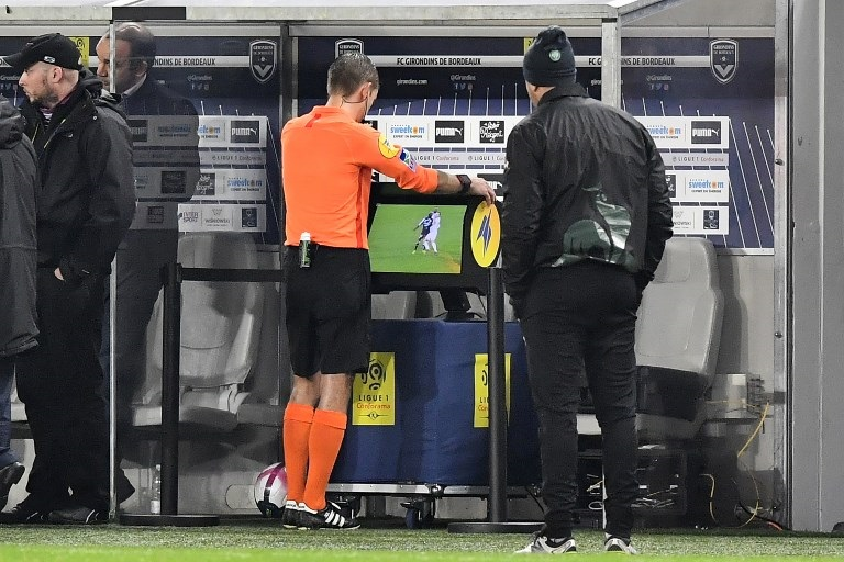 French referee Clement Turpin looks at the Video Assistant Refereeing (VAR) during the French L1 football match between FC Girondins de Bordeaux and AS Saint-Etienne at the Matmut Atlantique stadium in Bordeaux.