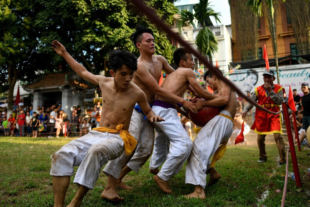 "Vietnamese men wrestle for the prized jackfruit wooden ball during the traditional ""Vat Cau"" festival on the fifth day of Lunar New Year celebrations."