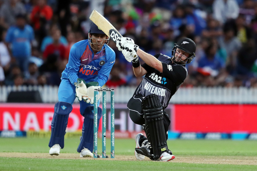 New Zealand's Colin Munro (R) plays a shot as India's MS Dhoni (L) looks on, during the third Twenty20 international cricket match between New Zealand and India.
