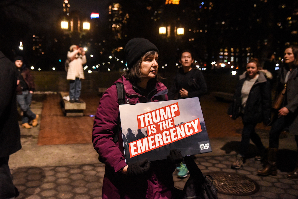 "A protester holds a sign that reads ""Trump is the emergency"" in front of Trump International Hotel in New York City."