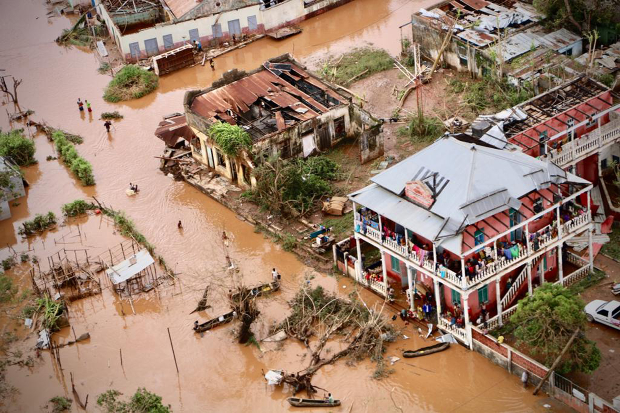People walk on the flooded street of Buzi, central Mozambique, on March 20, 2019 after the passage of the cyclone Idai.