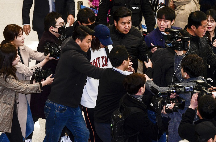 This picture taken on March 12, 2019 shows K-pop star Jung Joon-young (C)  surrounded by reporters as he arrives at Incheon international airport in  Incheon