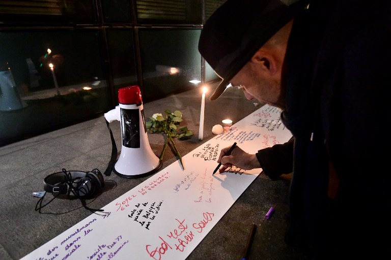 People write messages on a sheet of paper during a gathering to commemorate the victims of an attack on two mosques in New Zealand at the New Zealander Embassy in Brussels on March 15, 2019.