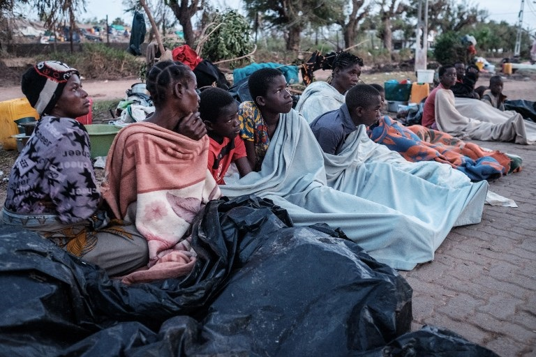 People who lost their home by the cyclone Idai wake up in the morning as they stay in a shelter on a street in Buzi, Mozambique.