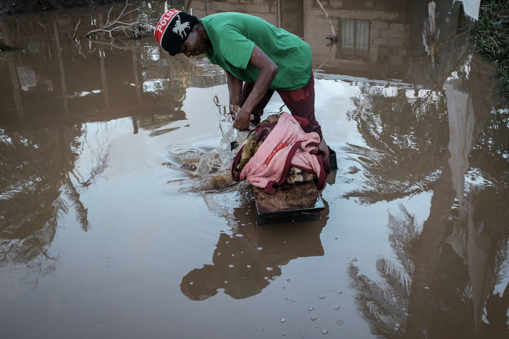 Lidia Mubando washes a blanket in flooded and muddy waters after Cyclone Idai hit the area.