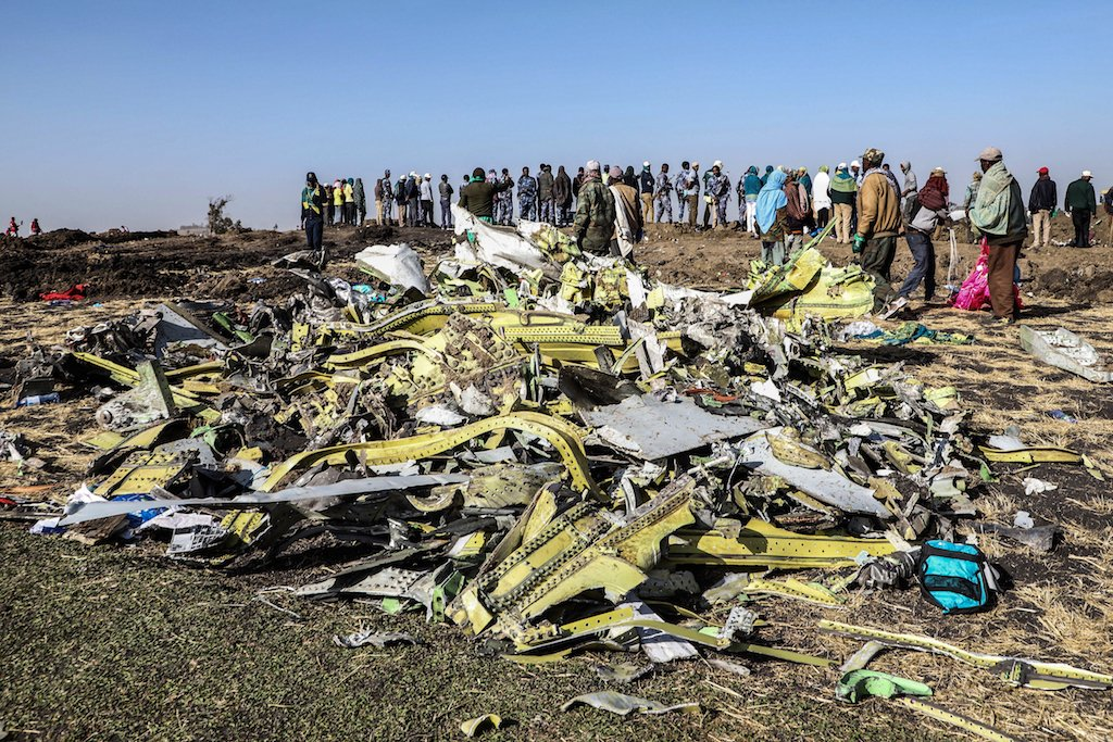 People stand near collected debris at the crash site of Ethiopia Airlines near Bishoftu, a town some 60 kilometres southeast of Addis Ababa.