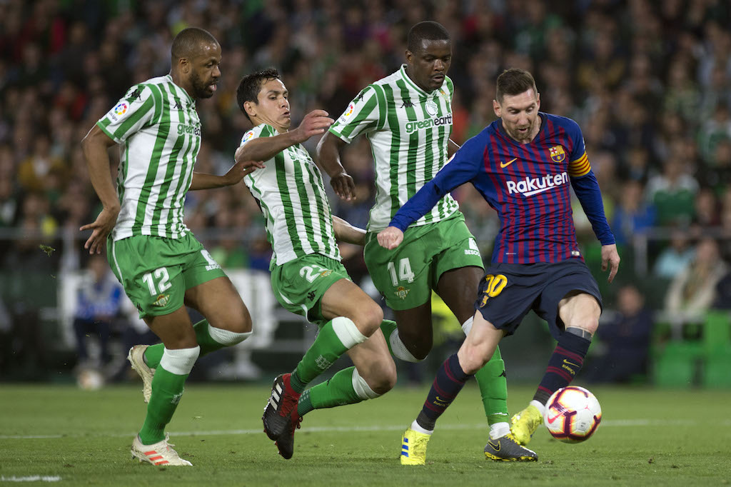 Barcelona's Argentinian forward Lionel Messi (R) shoots to score a goal during the Spanish league football match between Real Betis and FC Barcelona.