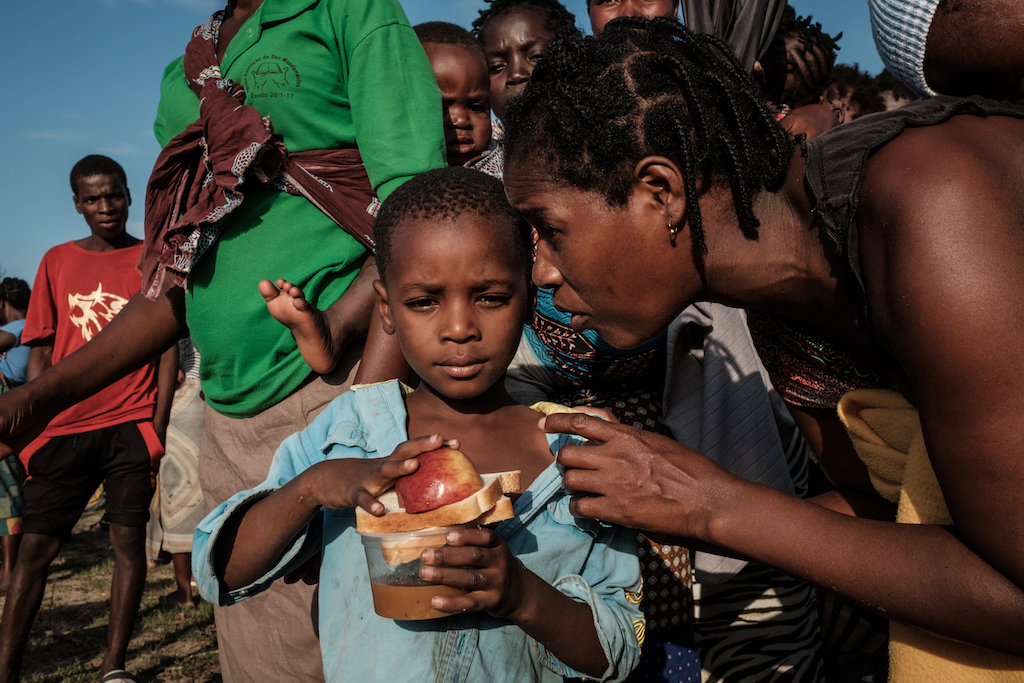 A child listens to his mother after receiving food distribution at an evacuation centre in Dondo just outside Beira.