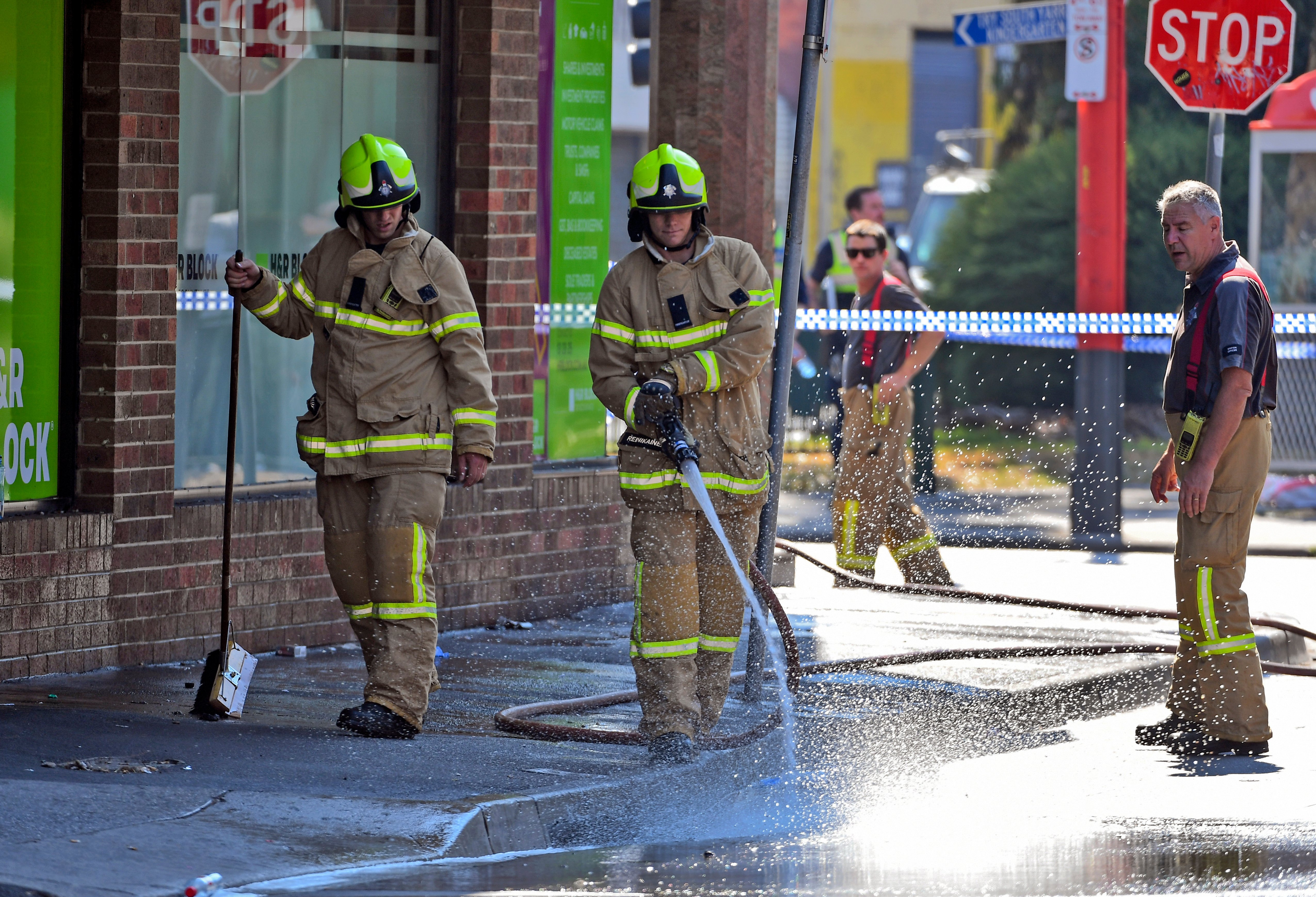 Firemen wash away bloodstains after a security guard was shot dead with another man fighting for his life after a drive-by shooting outside a popular Melbourne nightclub on April 14, 2019.