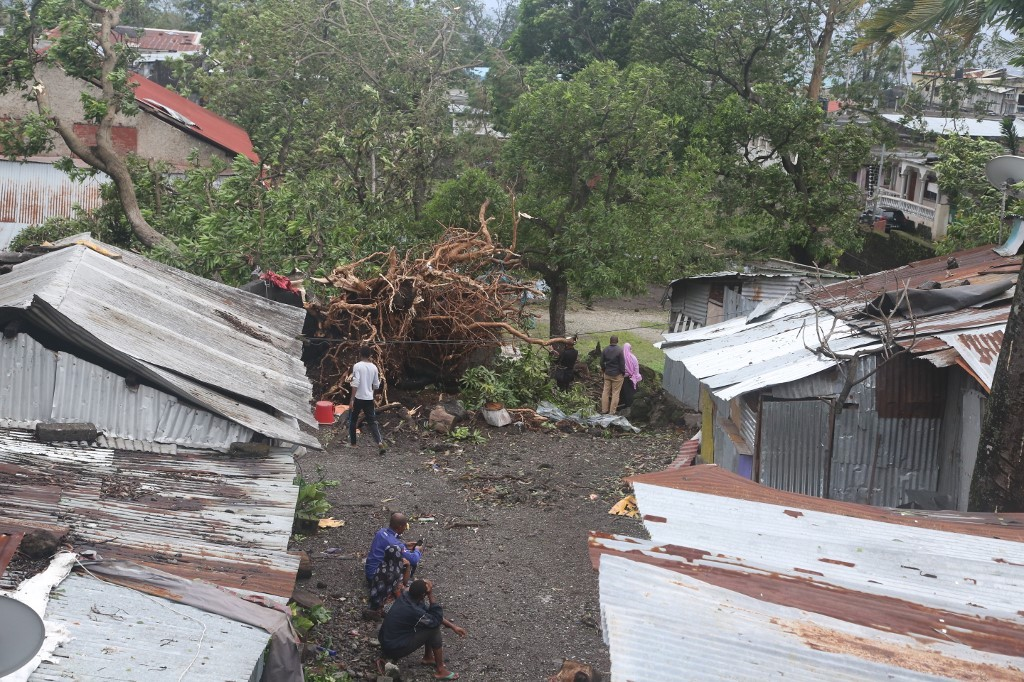 People stand by damaged houses and fallen trees on April 25, 2019 in Moroni after tropical storm Kenneth hit Comoros before heading to recently cyclone-ravaged Mozambique.