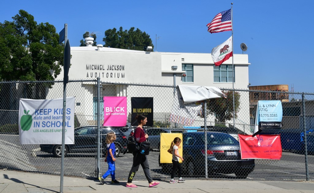 Pedestrians walk past the Michael Jackson Auditorium at Gardner Street Elementary school in Hollywood, California on April 25, 2019.