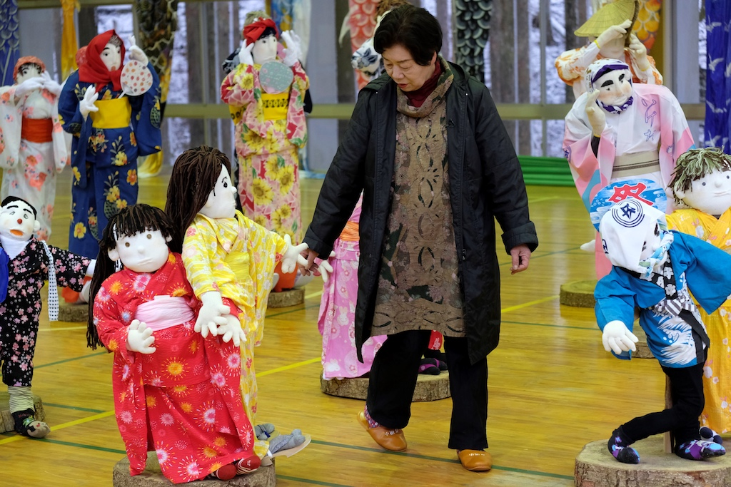 Local resident Tsukimi Ayano checking on a life-size doll displayed at an elementary school.