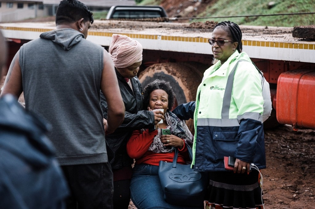A relative of one of the 9 victims is comforted by search and rescue team members after a mudslide following torrential downpours and flash floods destroyed houses, near Westcliff Secondary School in Chatsworth.
