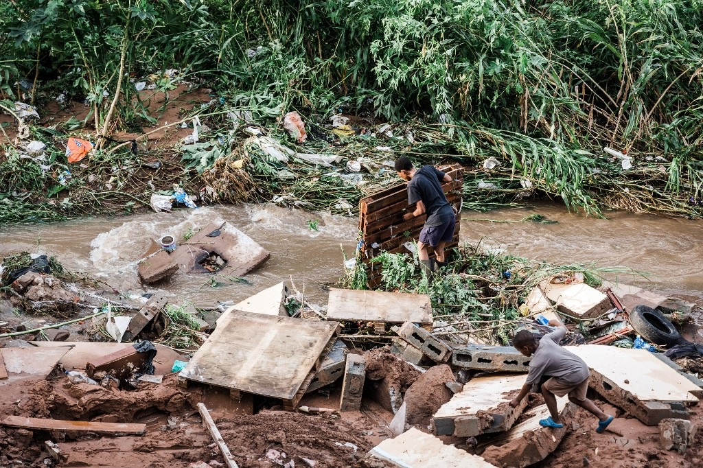 A man tries to salvage some of his furniture at an informal settlement of BottleBrush, south of Durban, after torrential rains and flash floods destroyed his home on April 23, 2019.