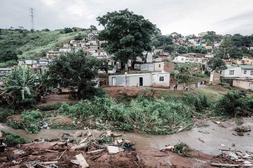 People abandon their homes at an informal settlement of BottleBrush, south of Durban, after torrential rains and flash floods destroyed their homes on April 23, 2019.