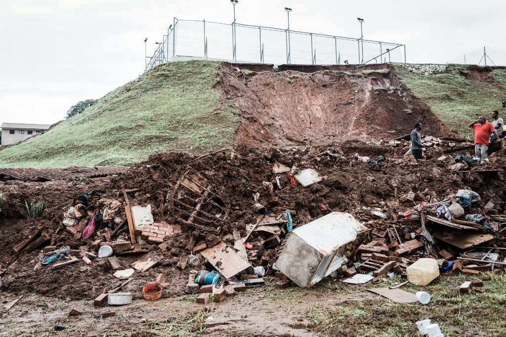 Police officers try to rescue people trapped in their homes destroyed in a mudslide following torrential downpours and flash floods, near Westcliff Secondary School in Chatsworth, south of Durban on April 23, 2019