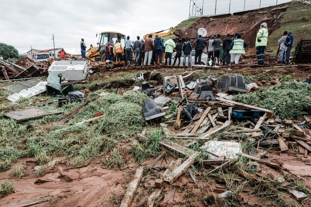 Police officers try to rescue people trapped in their homes destroyed in a mudslide following torrential downpours and flash floods, near Westcliff Secondary School in Chatsworth.