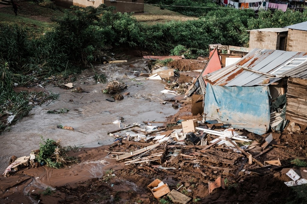 People abandon their homes after they were destroyed by torrential rains and flash floods at an informal settlement of BottleBrush, south of Durban, on April 23, 2019.