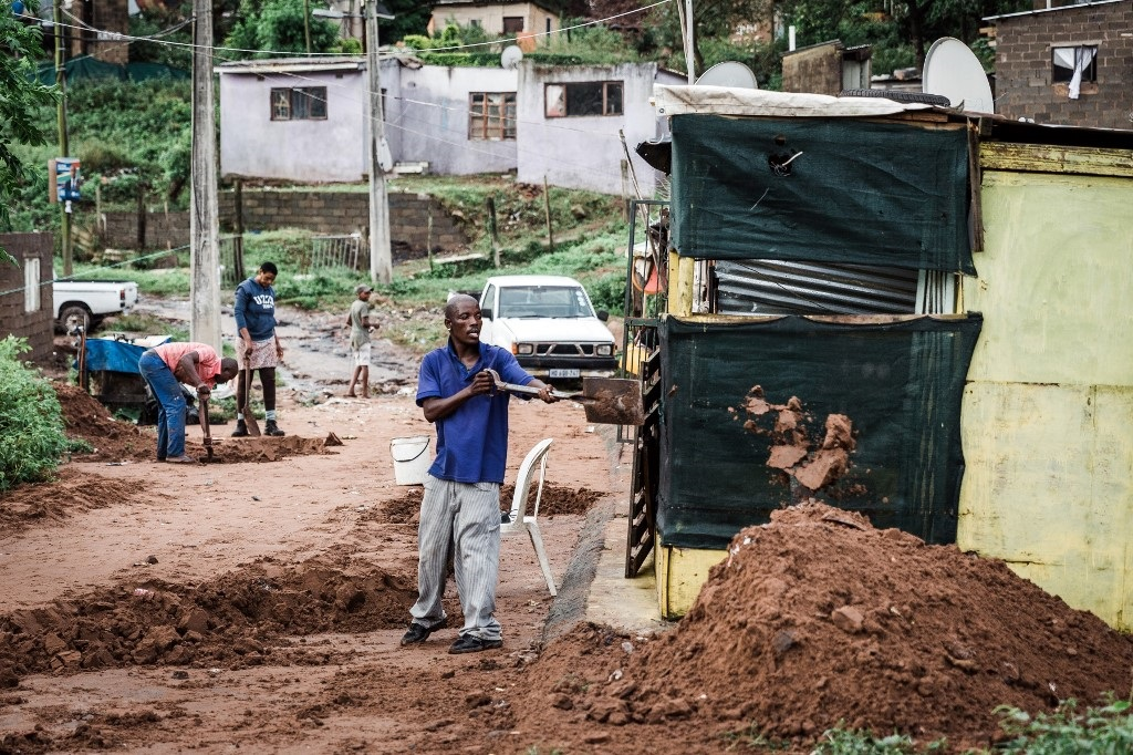 People begin to clear debris at an informal settlement of BottleBrush, south of Durban, after torrential rains and flash floods caused huge damages to their homes on April 23, 2019.