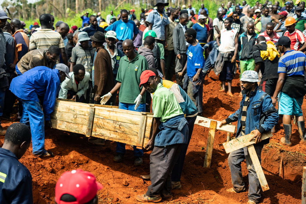 File: People carry coffins as mourners attend multiple burials at the Chimanimani Heroes Acre after the area was hit by Cyclone Idai.