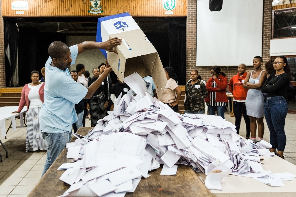 An Independent Electoral Officer (IEC) opens a ballot box as counting begins at the Addington Primary School after voting ended at the sixth national general elections.