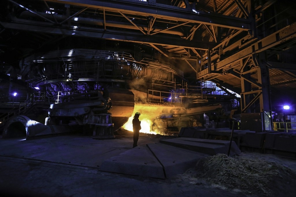A steelworker watches as molten steel pours from one of the Blast Furnaces during 'tapping' at the British Steel - Scunthorpe plant in north Lincolnshire, north east England.