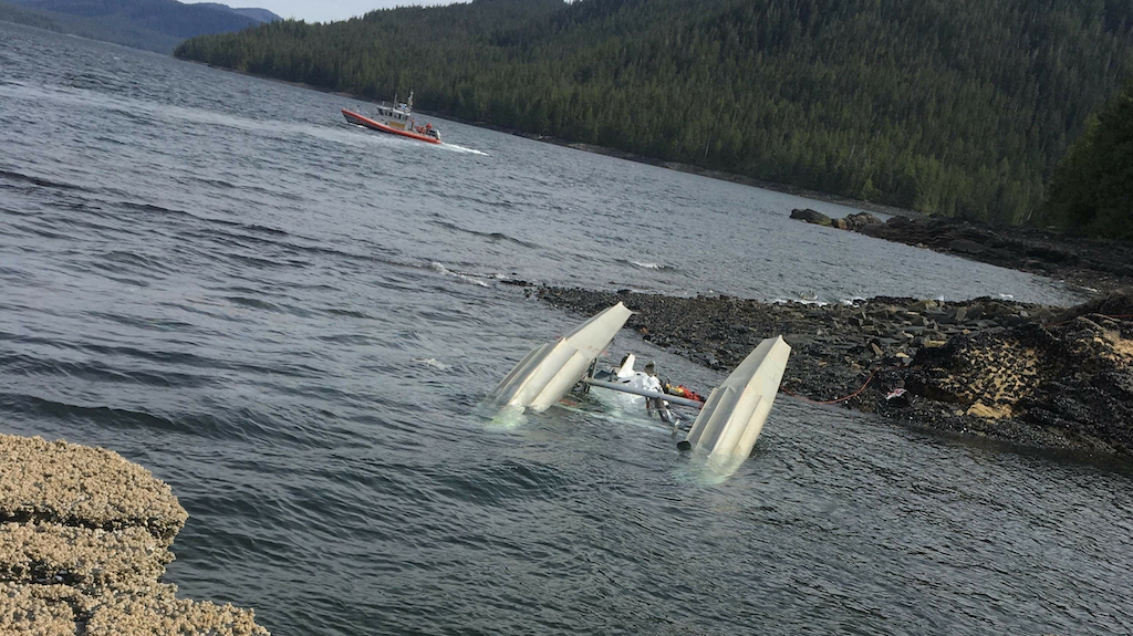 In this image courtesy of Ryan Sinkey and released by the US Coast Guard (USCG), a floatplane lies upside down after a mid-air collision with another plane.