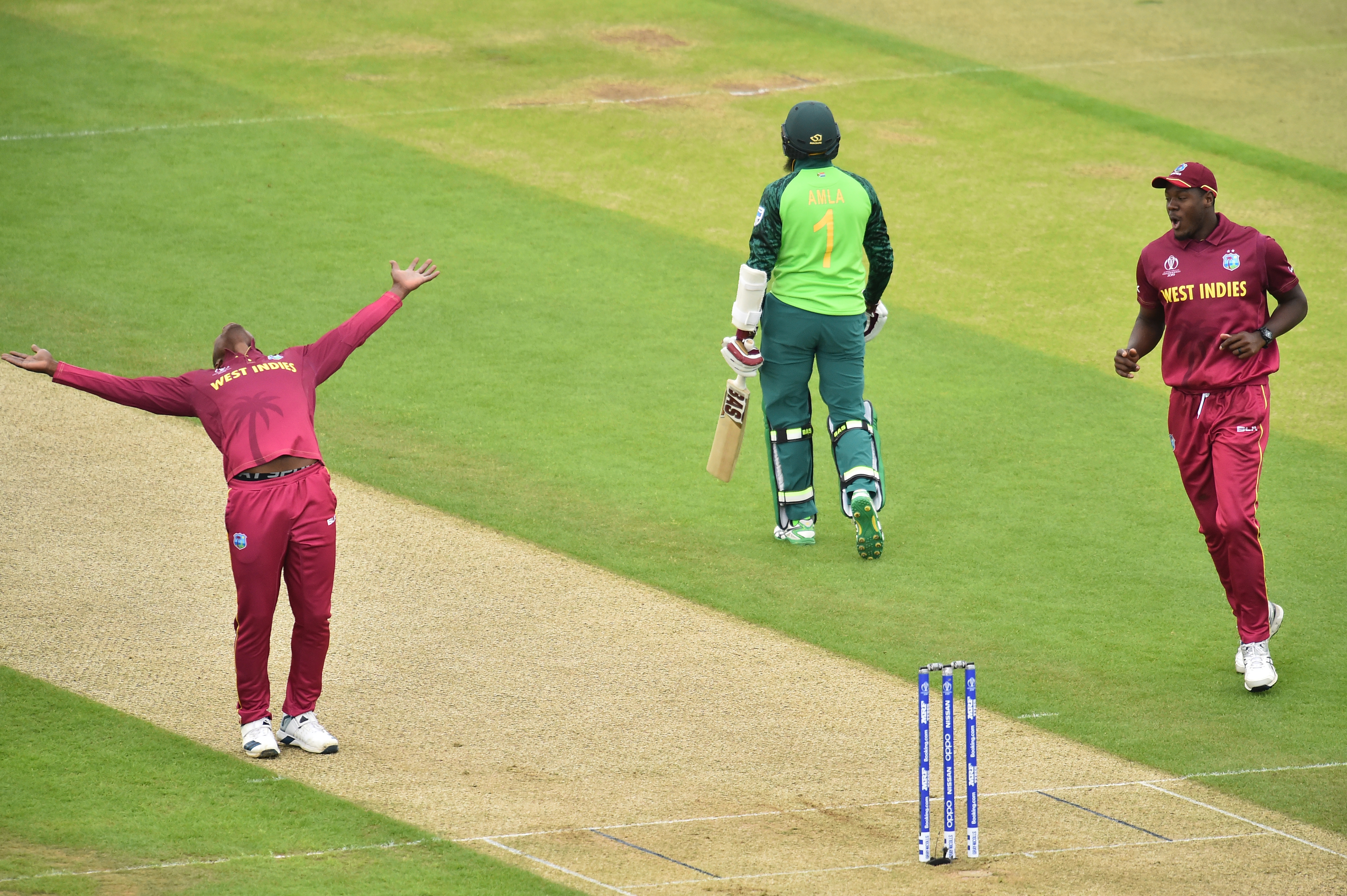 West Indies' Sheldon Cottrell (L) celebrates taking the wicket of South Africa's Hashim Amla (C) during the 2019 Cricket World Cup group stage match at the Rose Bowl in Southampton, southern England, on June 10, 2019.