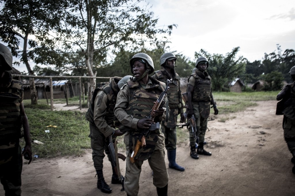 Soldiers from the Armed Forces of the Democratic republic of the Congo (FARDC) are seen gearing up as gunfire erupts close by.