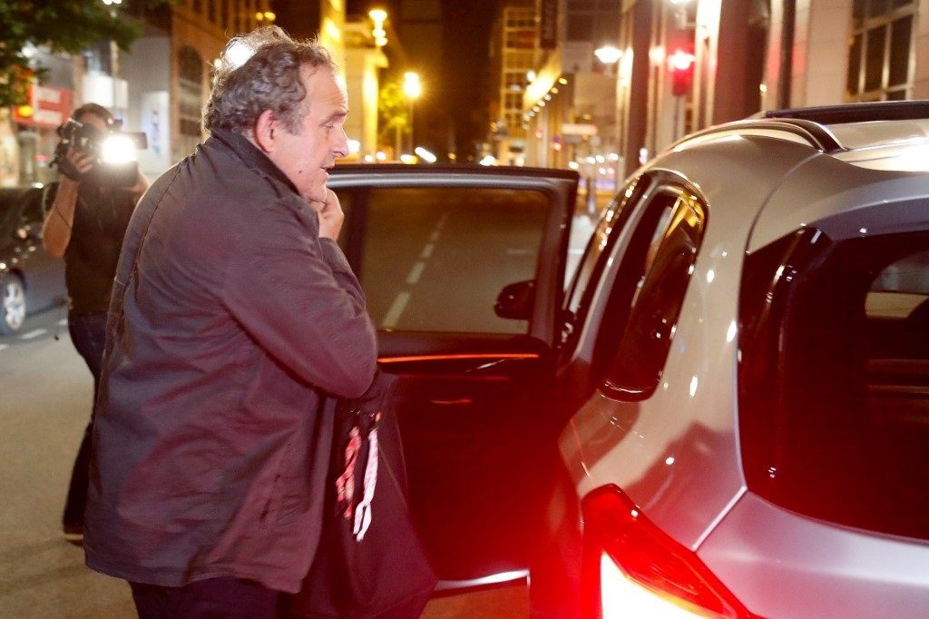 Ex-UEFA chief Michel Platini, flanked by his lawyer William Bourdon, talks to the media as he leaves the Central Office for Combating Corruption and Financial and Tax Crimes.